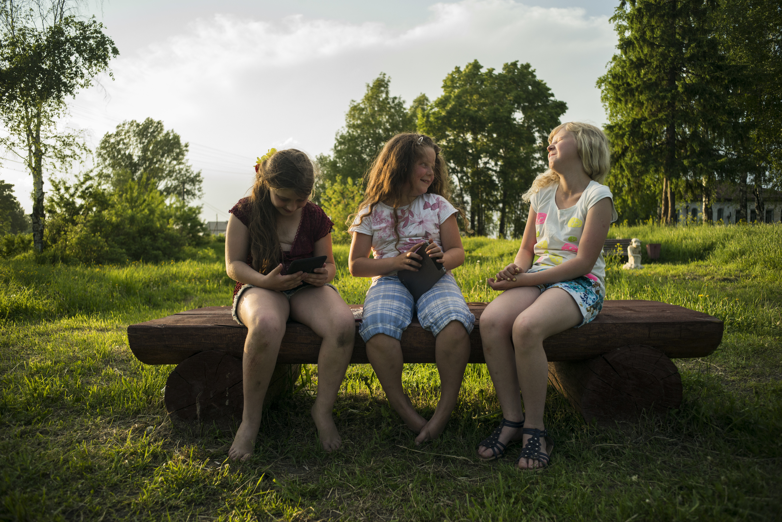 Three girls play on their electronic devices in a park in Saltvilchigotgzk near the Vitchigda River on May 30, 2015. (© Alicia Afshar)