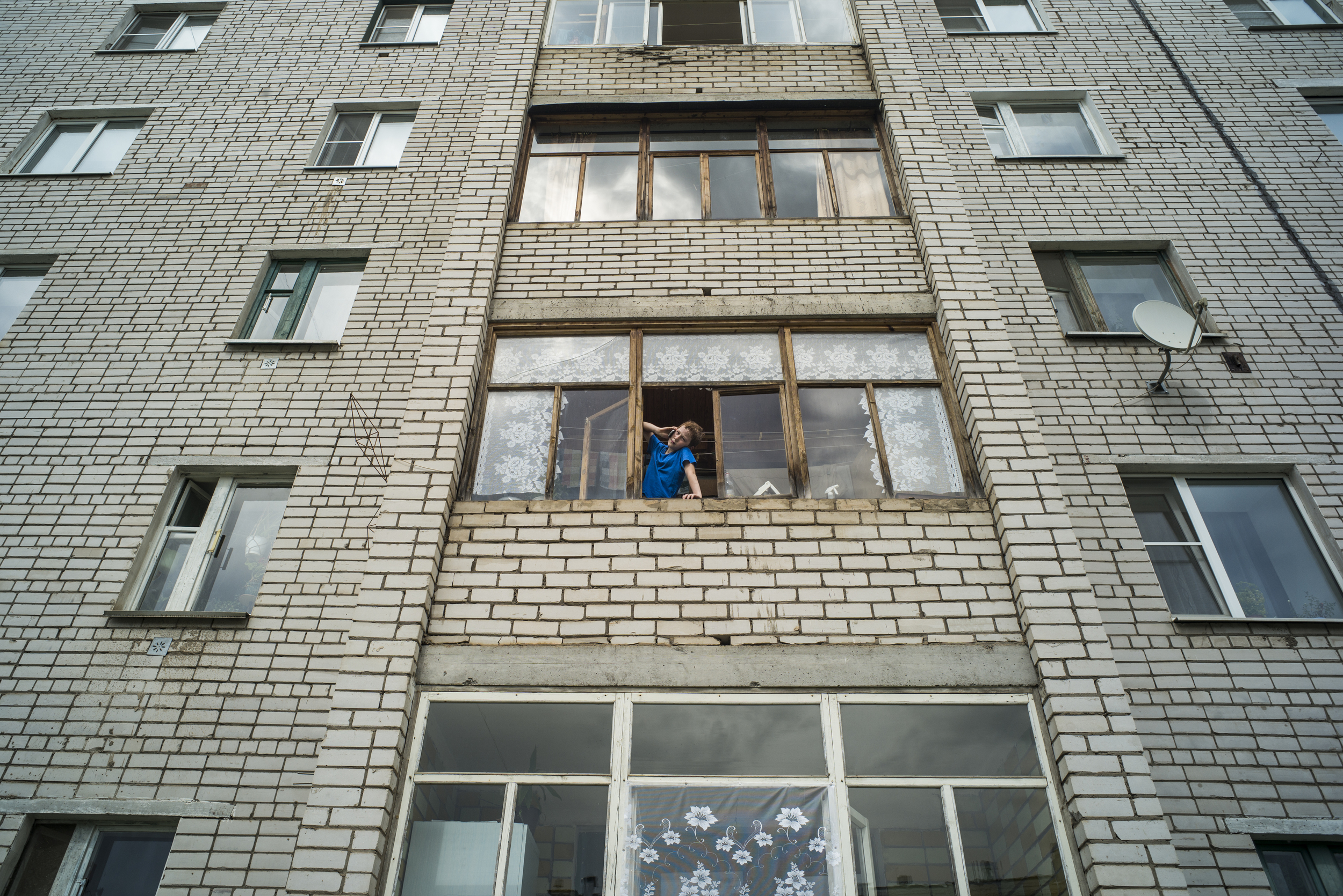 A young boy gazes out of the window of an apartment complex in the early morning of May 30, 2015 in the town of Kotlas in Arkhangelsk Oblast, Russia. (© Alicia Afshar)