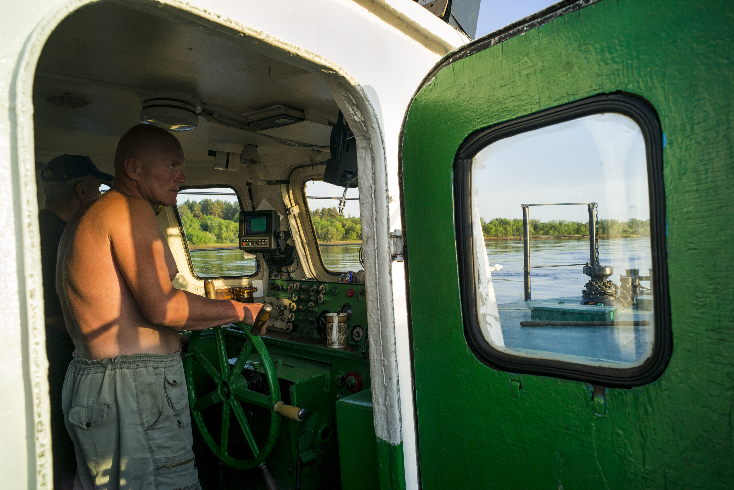 Captain Uri Mitriovitch gazes forward at what's to come and what will never change as he guides his ferry across the Vychegda River in Russia on May 30, 2015. (© Alicia Afshar)