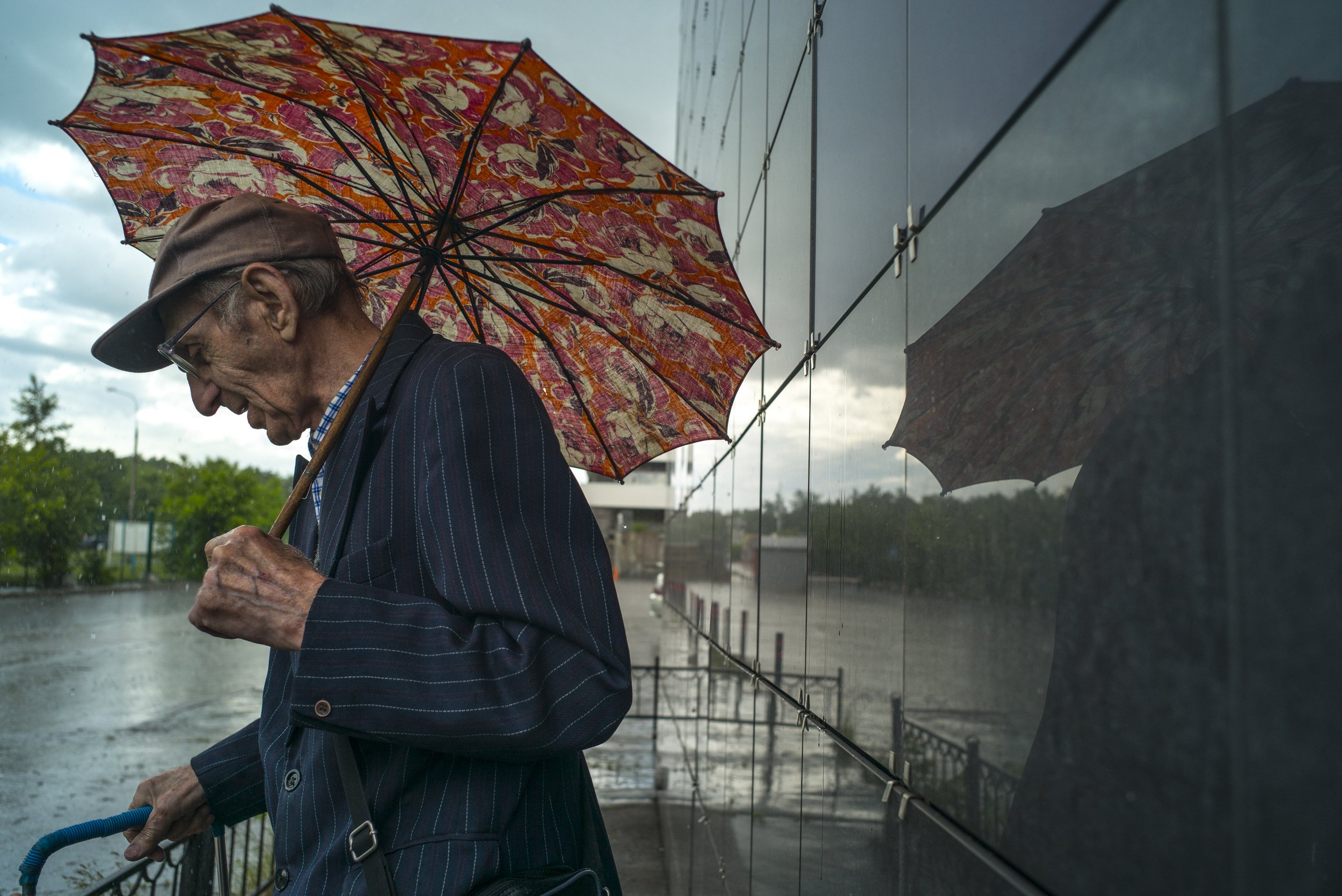Rain beats down as a man rests while on his way to the Izmailovsky flea market in Russia on June 5, 2015. (© Alicia Afshar)