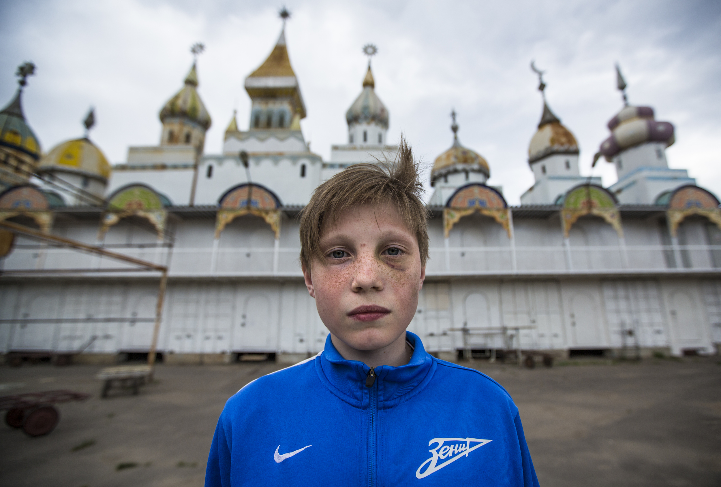 "After calling, ""Time out,"" an adolescent boy stops for a moment to pose for a portrait and then returns to playing Hide and Seek with his friends at the Izmailovsky flea market in Russia on June 5, 2015. (© Alicia Afshar)"
