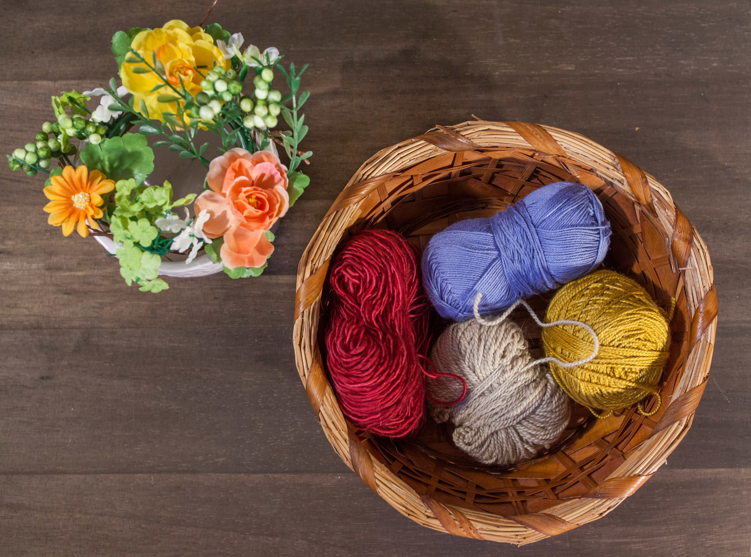 Pictured: flowers and four different types of fingering weight yarn.