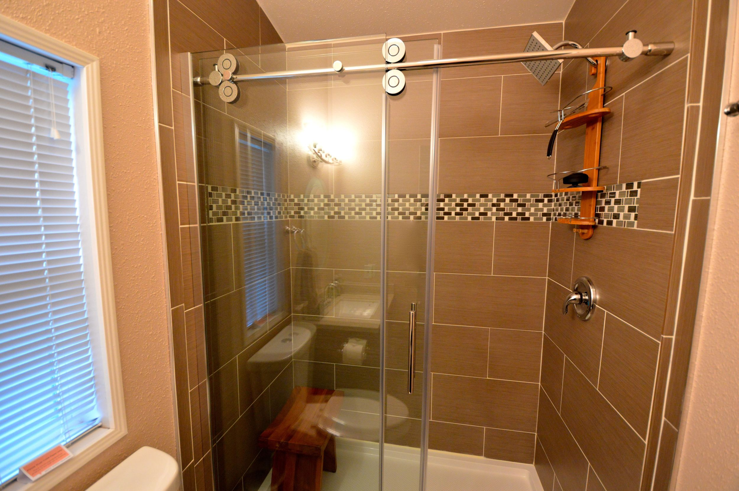 Guest Bathroom with updated & modern shower with full height rolling glass door.