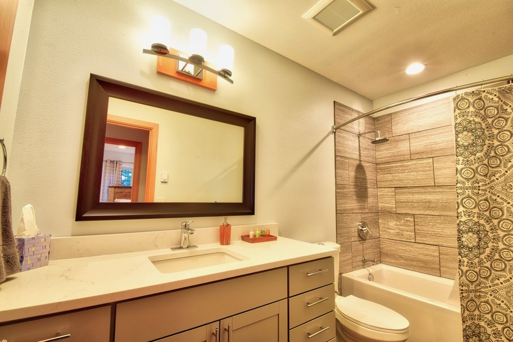 The Guest Bathroom features a deep soaking tub with a shower combination.