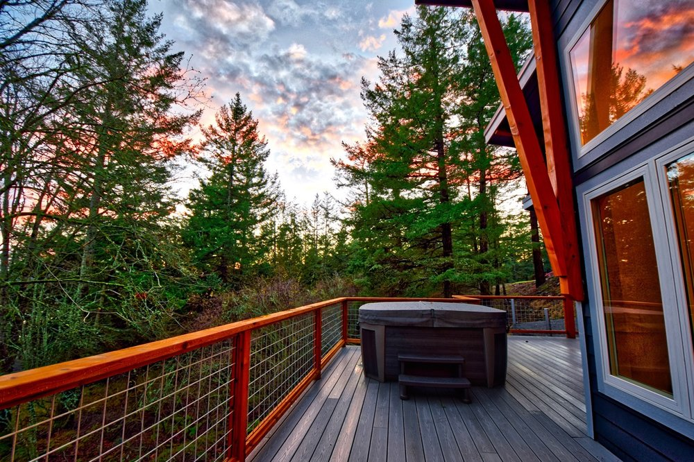 The large outdoor deck with filtered water views, outdoor dining table/chairs and Hot Tub.