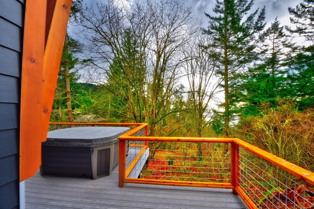 Relax in the hot tub located on the large outdoor deck with filtered views down to the water.