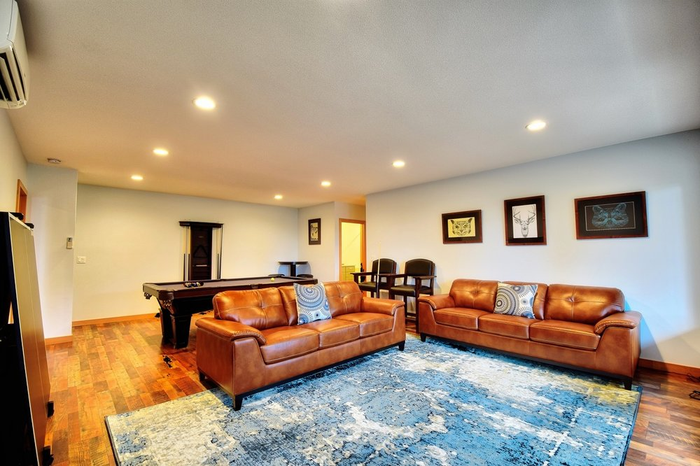 """After enjoying billiards and table tennis, guests can enjoy the two couches and 55"""" TV with Netflix and Amazon streaming services."""
