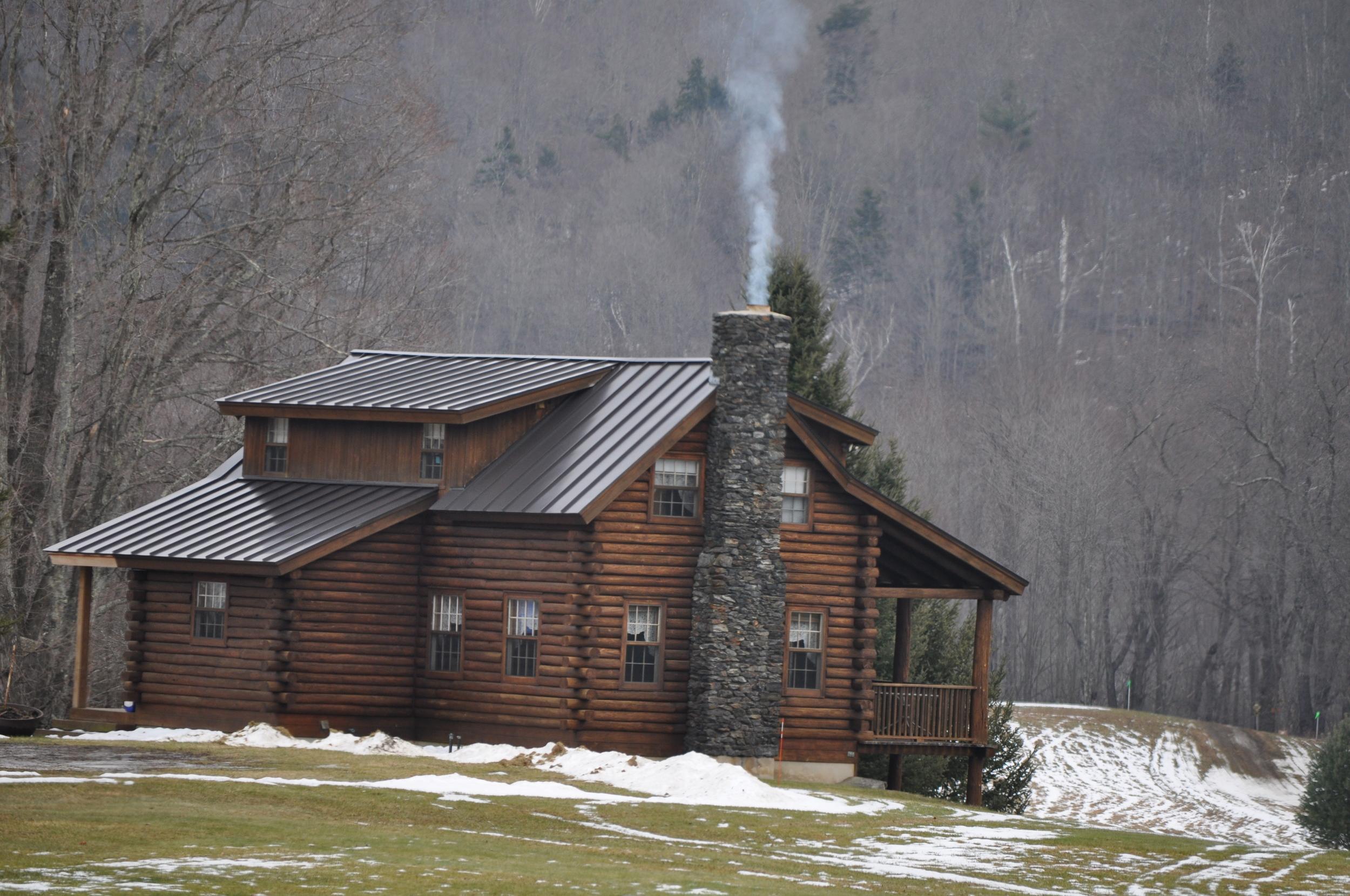 La cabaña de grotescos troncos redondos con el humo escapando de la chimenea. Foto: Pamy Rojas