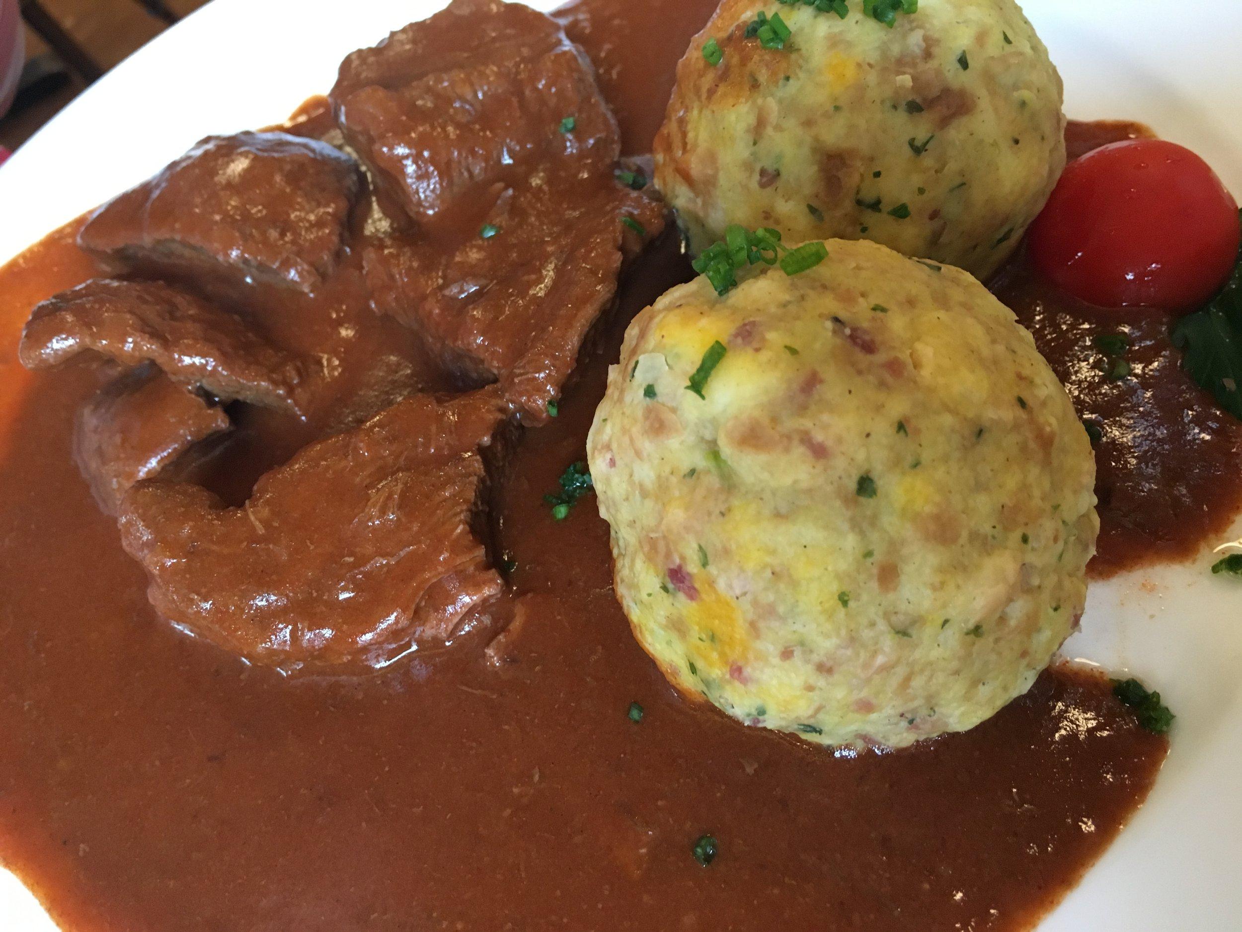 El acompañamiento típico en las comidas se conoce como Knödel. Parecido a una albóndiga pero preparado con leche, huevo, harina y muchas veces speck (tocineta ahumada) o queso. Aquí acompañado de Gulash, una receta húngara para carne guisada.   ¡Probamos varias recetas y la que tiene tocineta fue nuestra favorita! Foto: Bruny Nieves