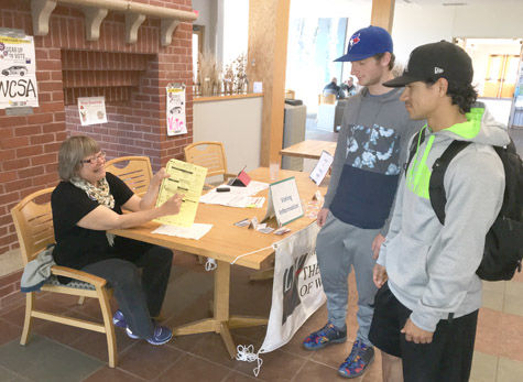 """Sara M. Chase/Staff Photo  Mary Rehwald of the League of Women Voters/Ashland-Bayfield Counties encourages Northland College freshman Ben Matteson and NC junior Xavier Baez to """"Gear Up to Vote,""""showing them a sample ballot."""