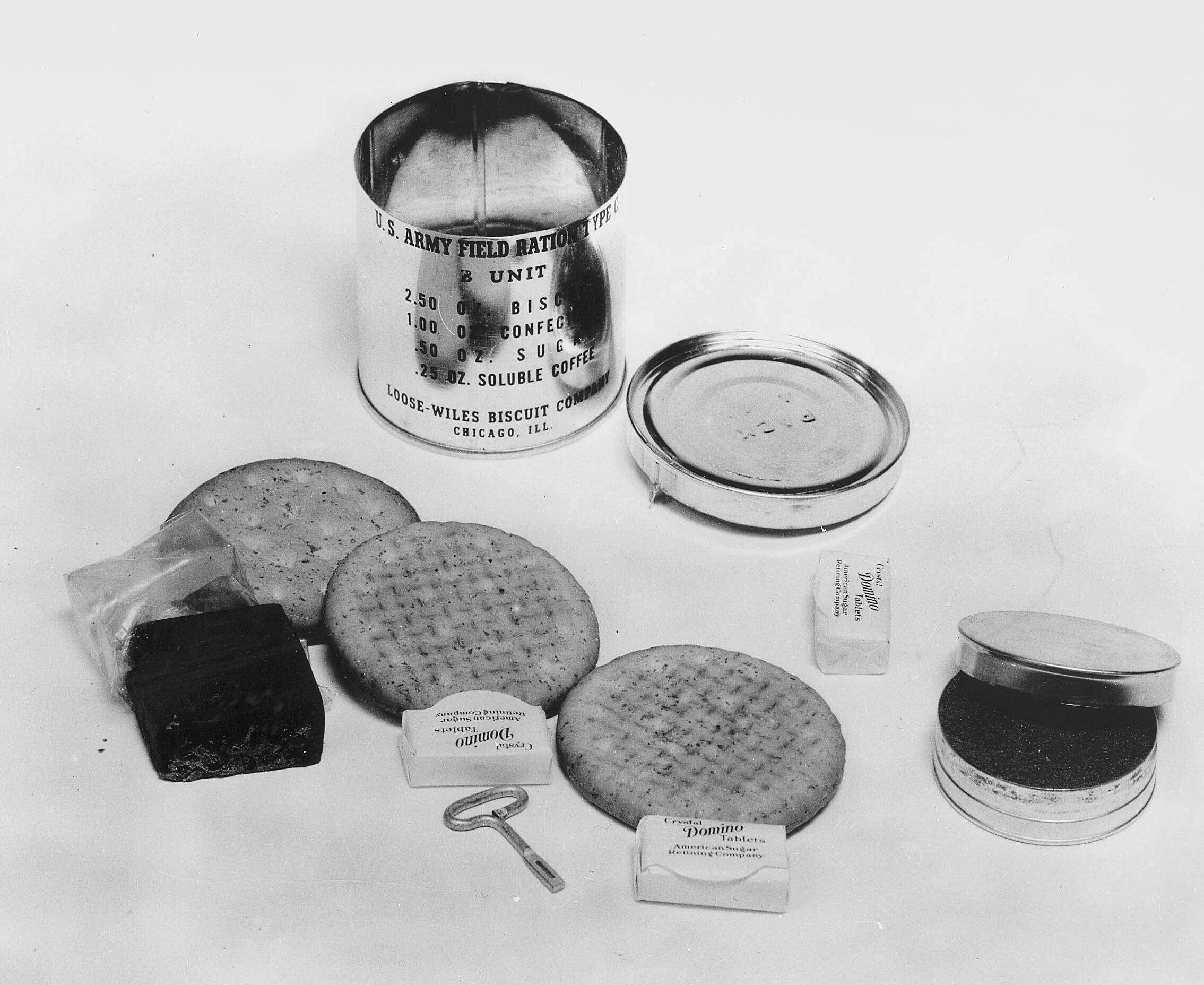 """A 1941 C Ration B unit, with contents: 3 biscuits, cellophane wrapped chocolate fudge, 3 pressed sugar cubes, and a small tin of soluble (instant) coffee. Can label indicates contents and supplier: """"2.50 oz Biscuit, 1.00 oz Confection, .50 oz Sugar, .25 oz Soluble Coffee Loose-Wiles Biscuit Company, Chicago Ill."""" United States Army, 1941"""