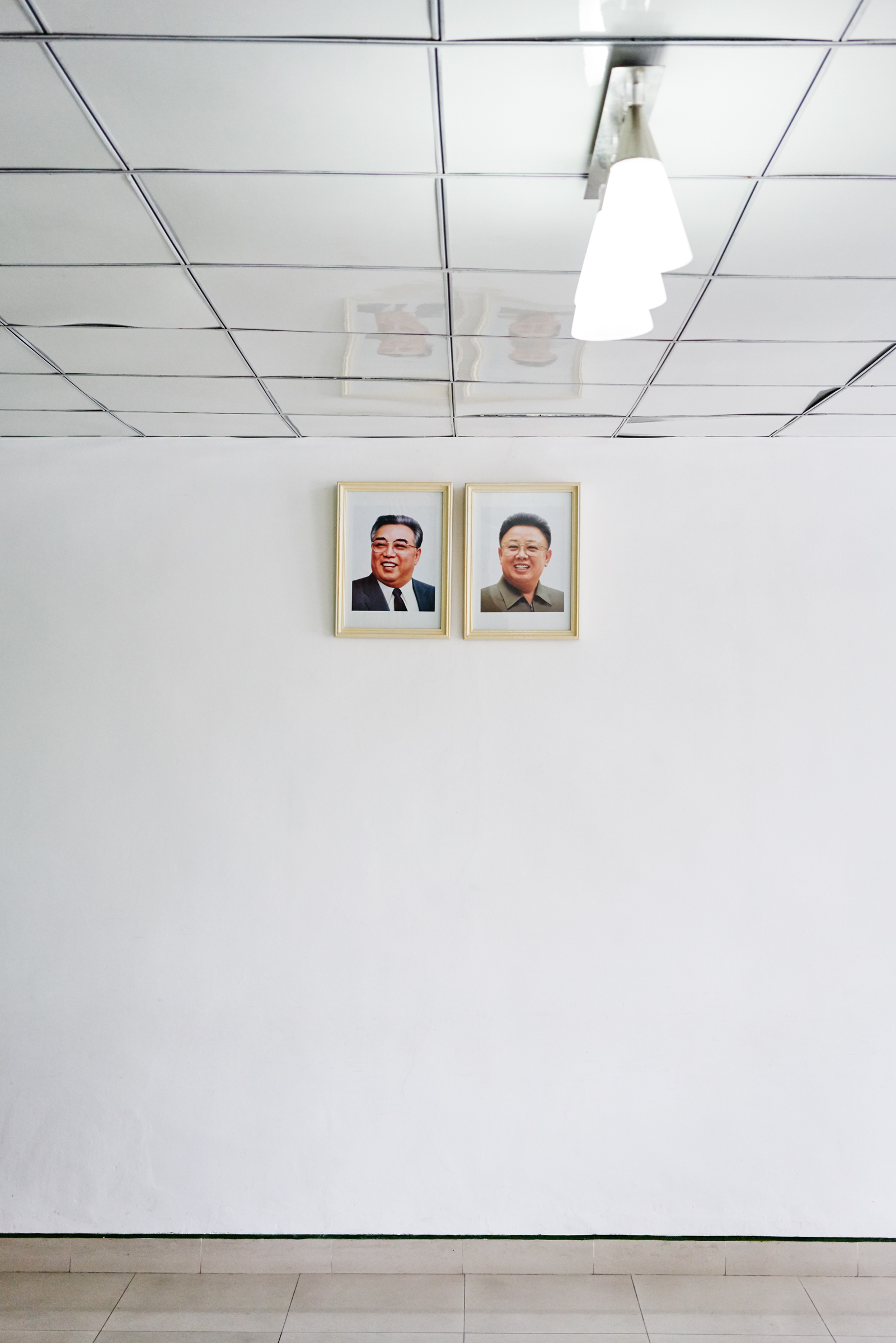 A photo of Kim Il-Sung and Kim Jong-Il hang in empty room Kaesong, NK