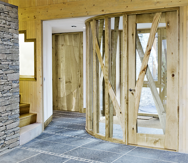 Plummerswood main lobby with curved glazed screen to the right and panelled wood door to the back - both made from oak and spalted beech.