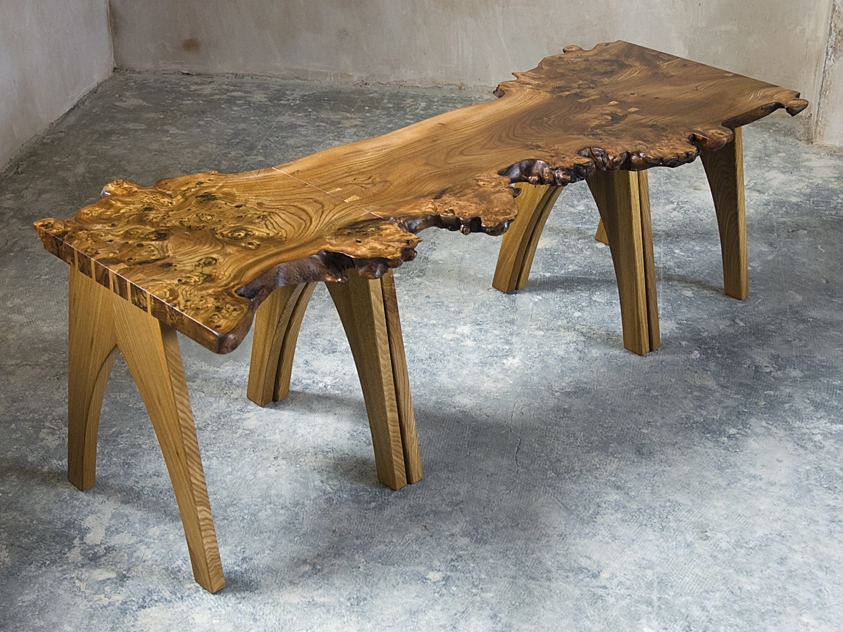 Natural edge coffee tables in burr elm with dovetailed arch legs.