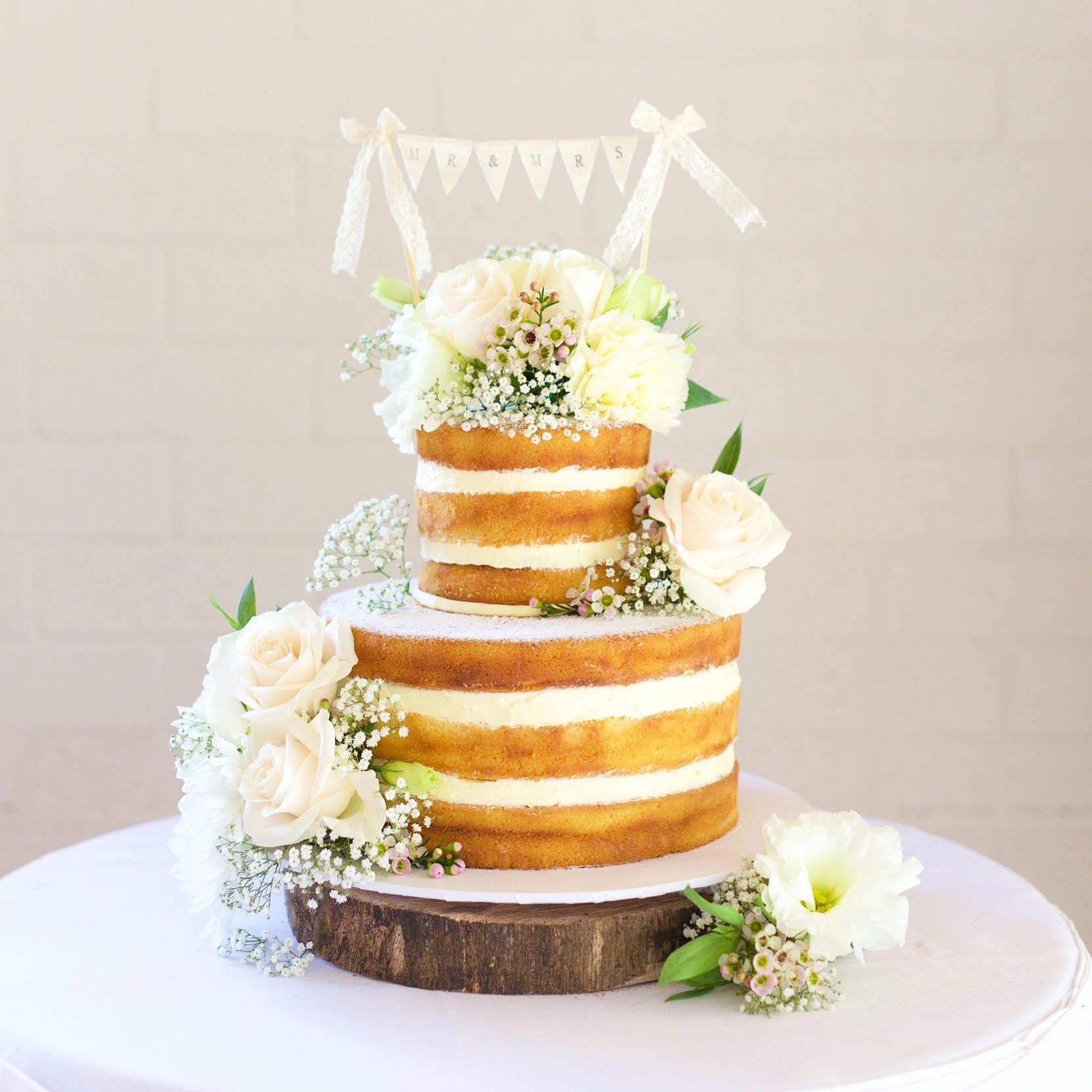 A Naked Wedding Cake Adorned With Gorgeous,Fresh Blooms. Cake & Flower Styling By Byron Bay Cake Boutique.