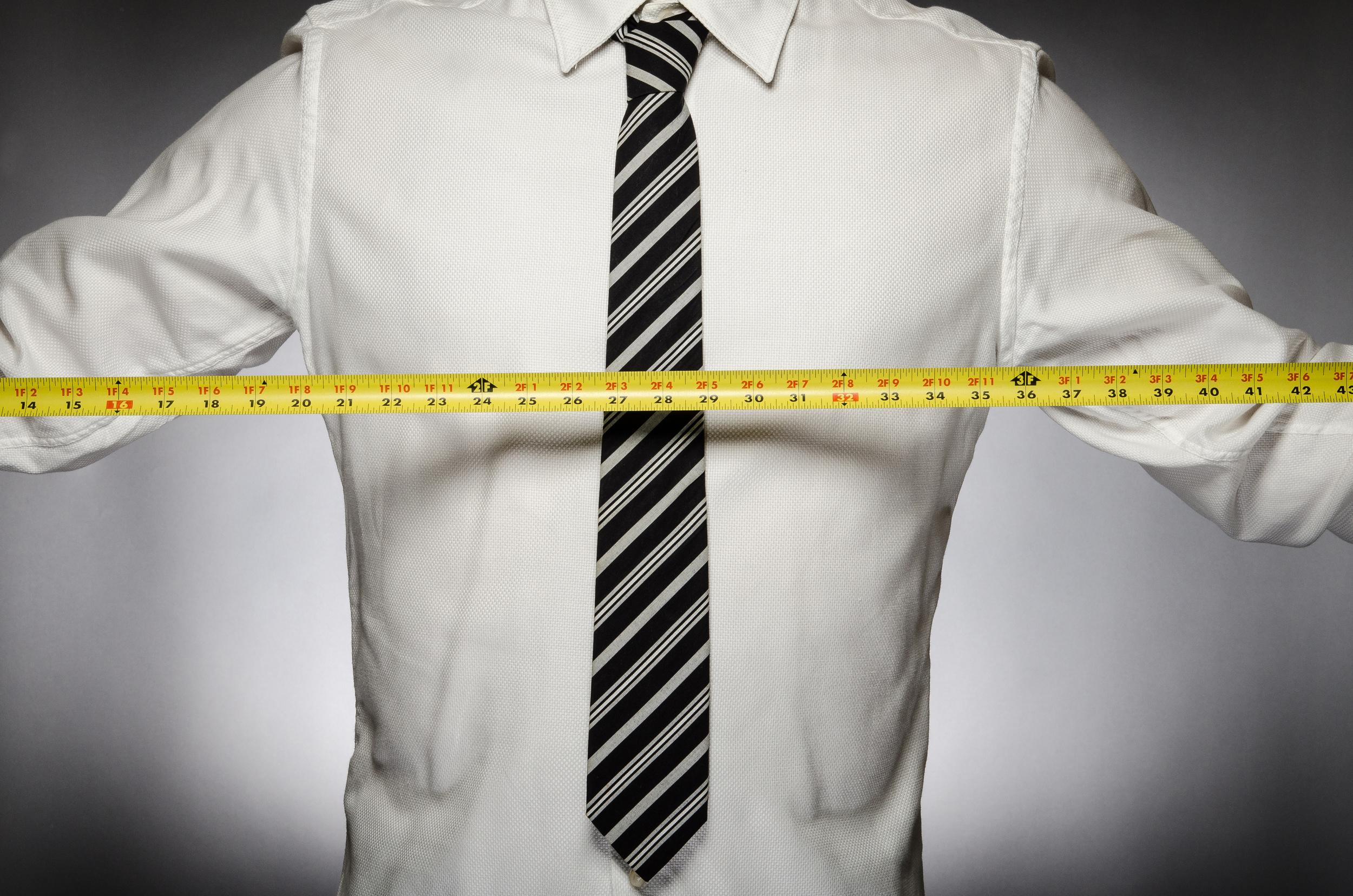 Man wearing tie holding tape measure