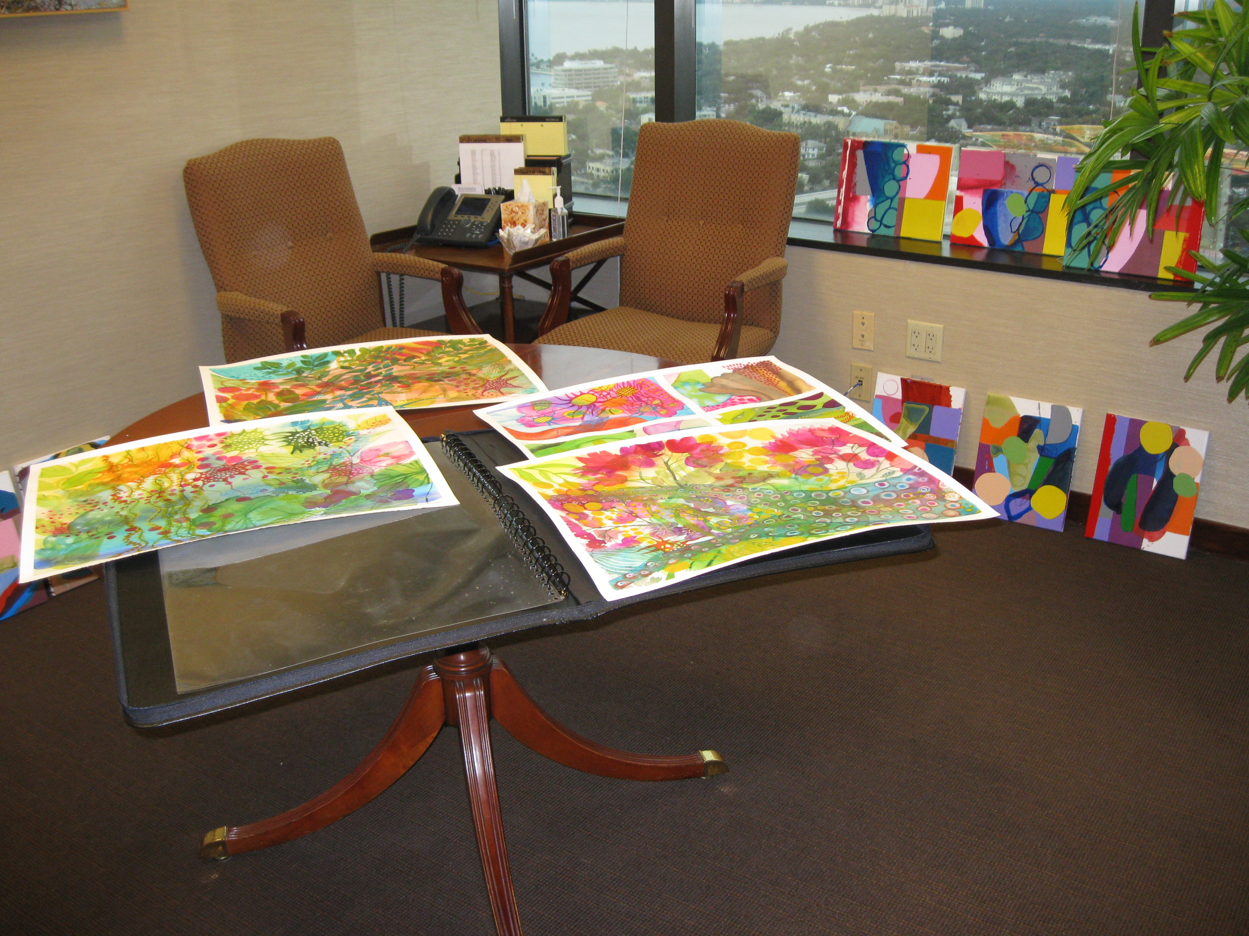 Watercolors displayed on table by Sara Golding Scher; acrylic on canvas series, leaning on right, by George Anderton