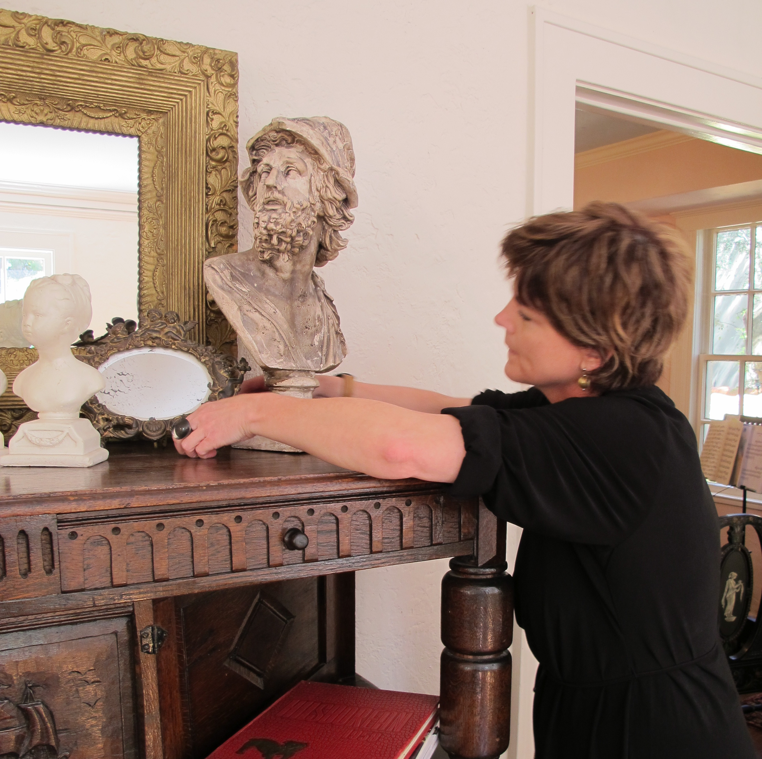 Working in client home arranging historical pieces in complimentary vignettes