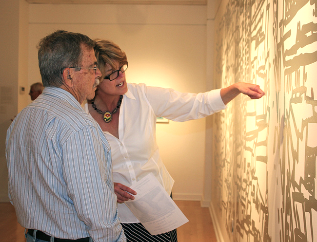 "Katherine Gibson explains to Bruce Marsh how Gallery 221's featured artist, Josette Urso, ""weeds"" her 20' vinyl drawing to reveal negative space. Photograph courtesy of Hillsborough Community College."