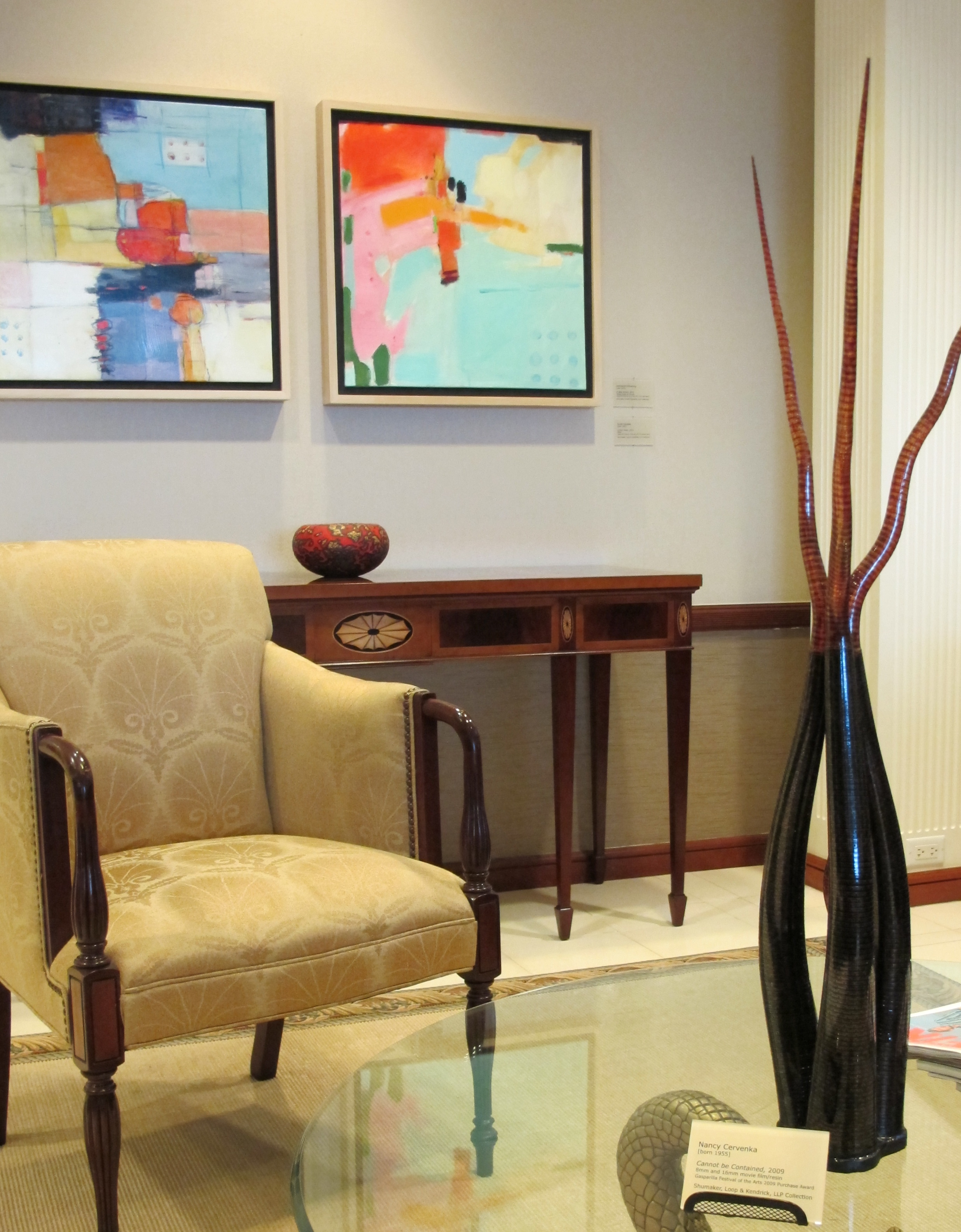 Corporate lobby rearranged with new artwork, mixed media paintings by Tony Eitharong, and a sculpture by Nancy Cervenka, made from strips of film.