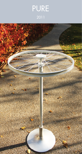 A cloth rack that is crafted with an abandoned bicycle wheel and a broken swivel chair
