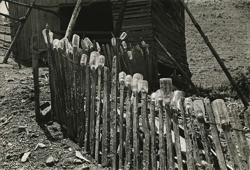 """Untitled [Shack and fence with glass jars],   ca. 1935. Vintage gelatin silver print, Signed in ink on print verso. Inscription in pencil by Stackpole: """"Here is a subject I might have done better with a large camera, but because I made it in a stranger's back yard I had to work fast before any objections arose. Contax II with Tessar 50 mm f3.5 lens, 1/125 sec F9 Super X film"""". Image measures 6 3/8 x 9 3/8 inches. Inventory #C0656.  Terms  