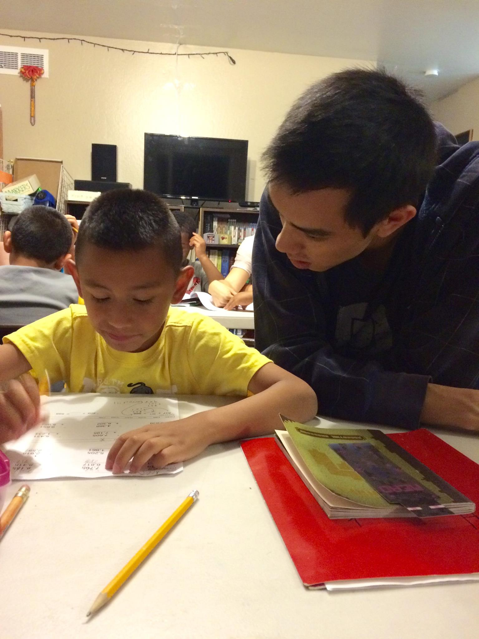 A young boy receives homework help from volunteer, Jordan, during bible club plus.