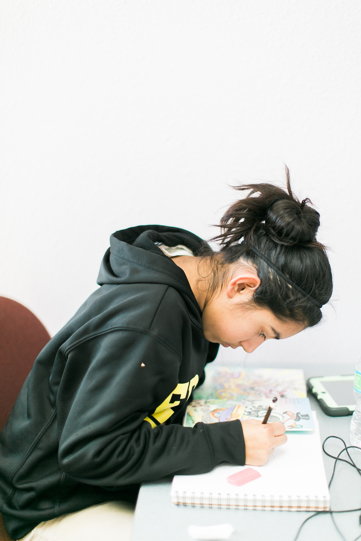 This youth meets with Sydney as she completes art homework.