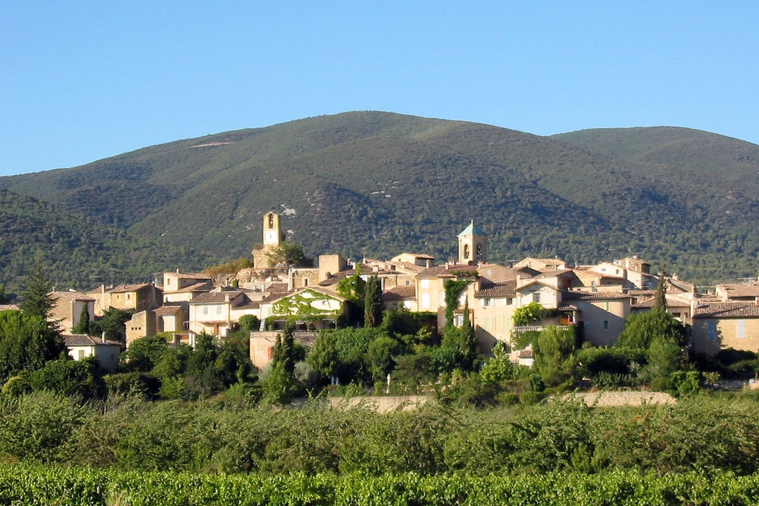 Lourmarin as seen across vineyards and orchardswith the Luberon hills as a backdrop