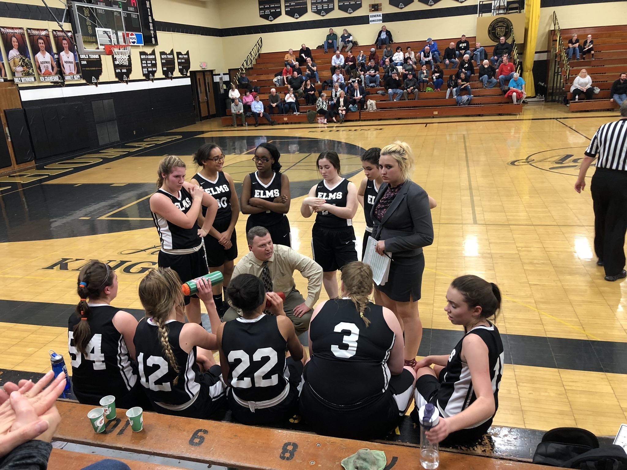 Members of the Elms Varsity Basketball Team discuss strategies with their coaches during a season game.