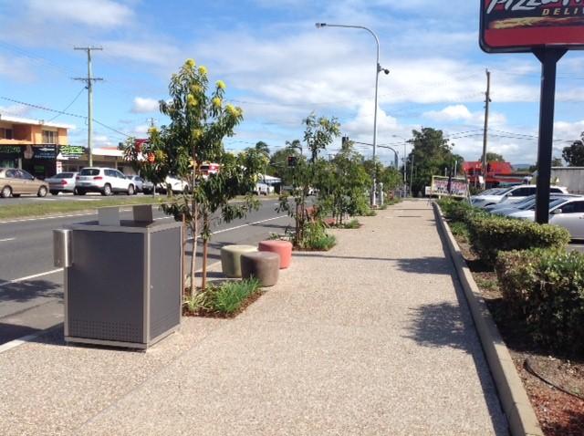 street view on wynnum road, featuring new pavement, street trees, gardens, bins and urban stools.