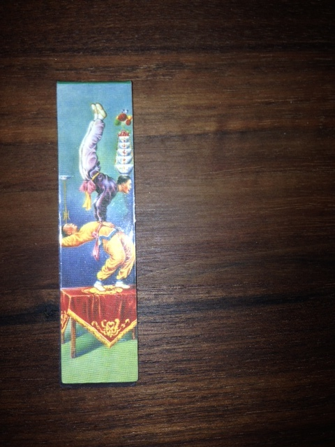 Bookmarks!   Another one from my collection. I brought this one back from a bookseller trip to Beijing. I bought it as a souvenir to remind me of our evening at the  Chaoyang Theater Acrobatics Show . The bookmark folds over and the two sides are magnetic, hugging the page tightly. I love the acrobats painted on the front, but I love even more that I can imagine the others already flying through the air to the next page.