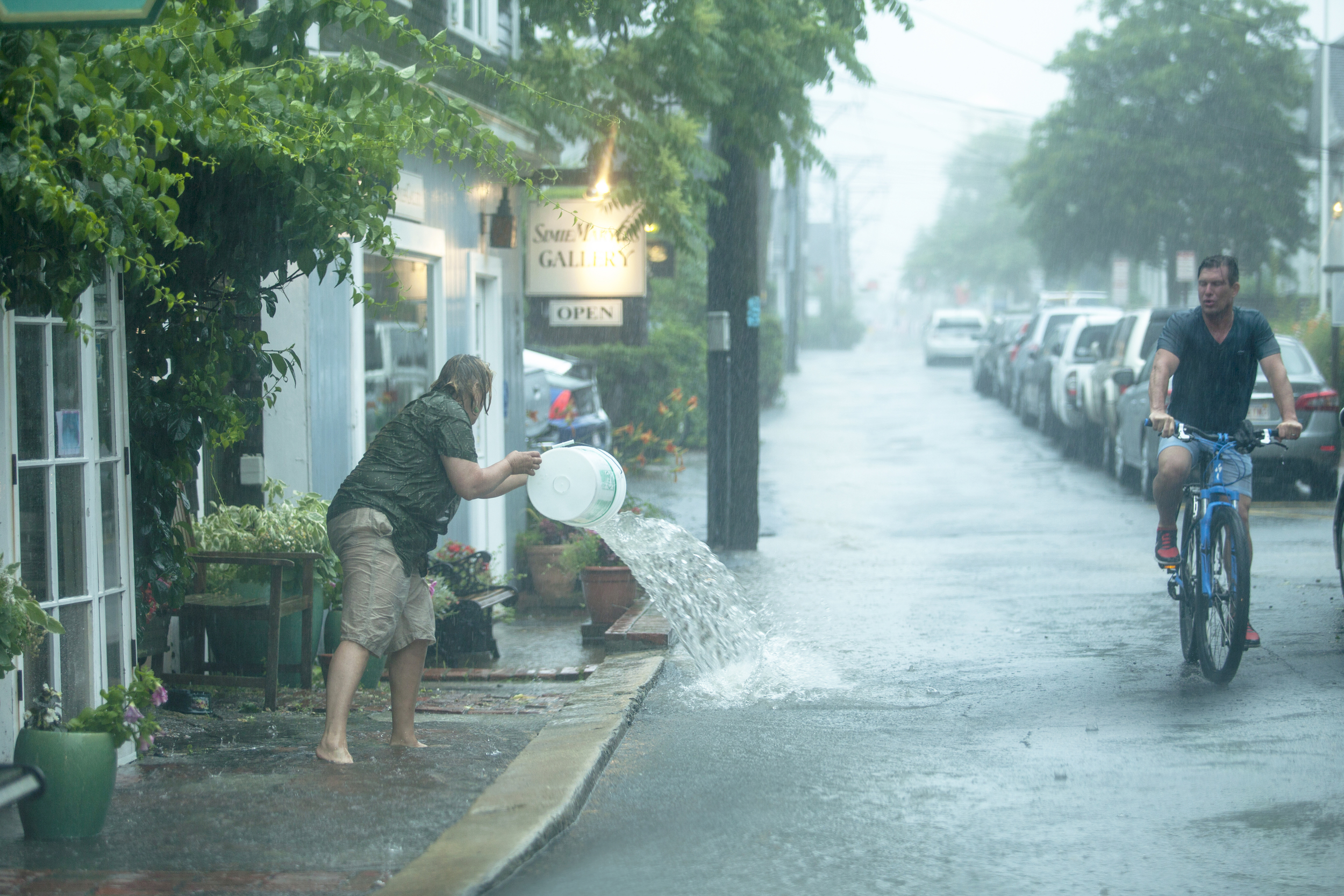 Gallery owner uses bucket to clear water that was flooding her store front as man on a bike passes by.
