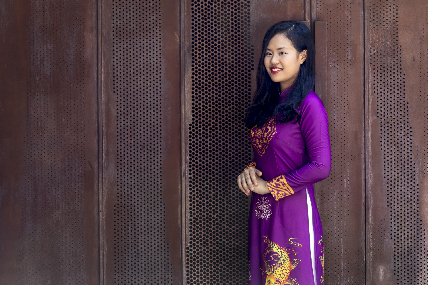 Purple Ao Dai on a rustic background.