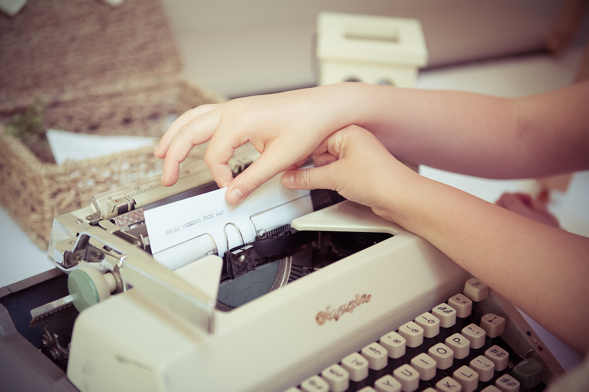 two girls typing on an old fashioned typewriter