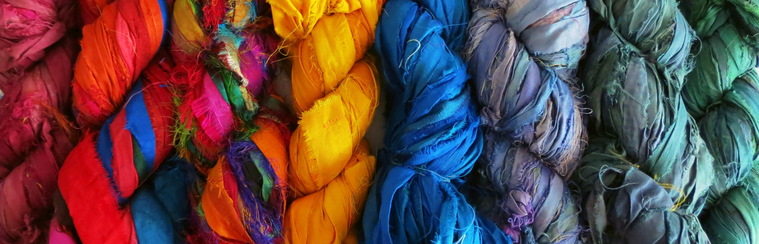 Recycled sari silk ribbon bundles from women cooperatives in India.