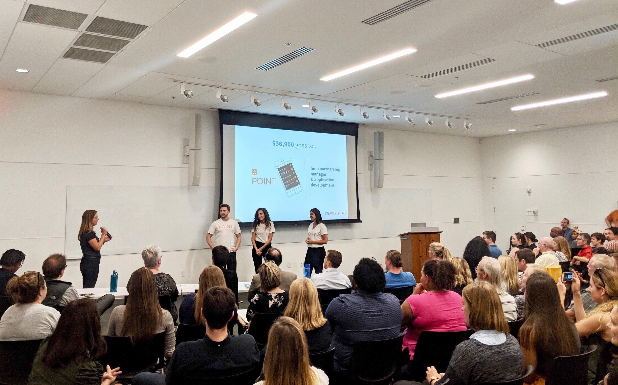 Suzy Bureau, Founder of  GiveBackHack , announces prizes at Sea Change Columbus 2018.
