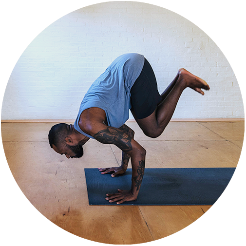 Justin is jumping back to chaturanga from a seated yoga posture.