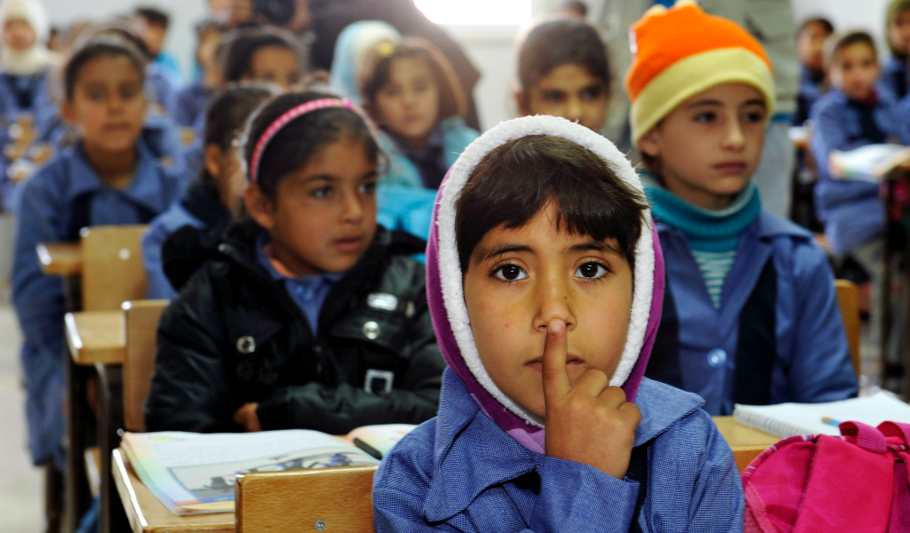 In this 2012 photo, children inside a classroom at Za'atri refugee camp, host to tens of thousands of Syrians displaced by conflict, near Mafraq, Jordan. flickr/un_photo