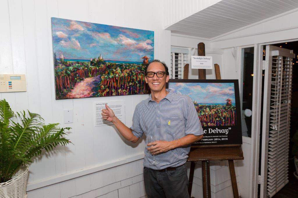 "My collector pointing to the original painting "" At Delray Beach"" shown above the poster, ""Nostalgic Delray""."