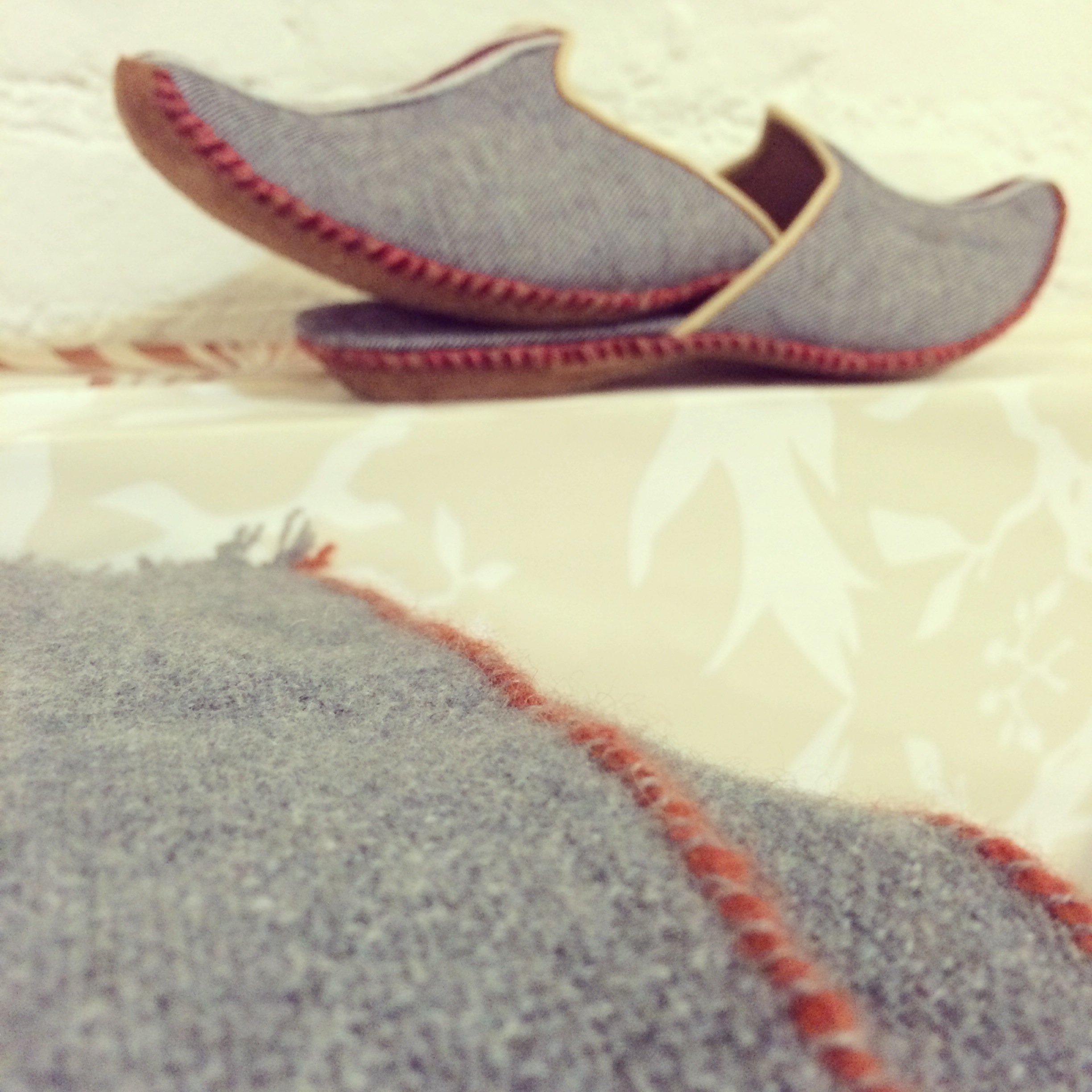 Handmade ottoman slippers made from selvedge denim by craftsmen in Sarajevo with cashmere throw by Teixidors