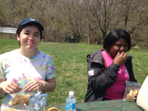 Claire and A'Lexus picnic on their lunch break at the National Arboretum during a City Kids canoe trip