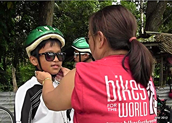 In the Philippines, a BfW volunteer fits a child with a helmet./Photo courtesy of Bikes for the World