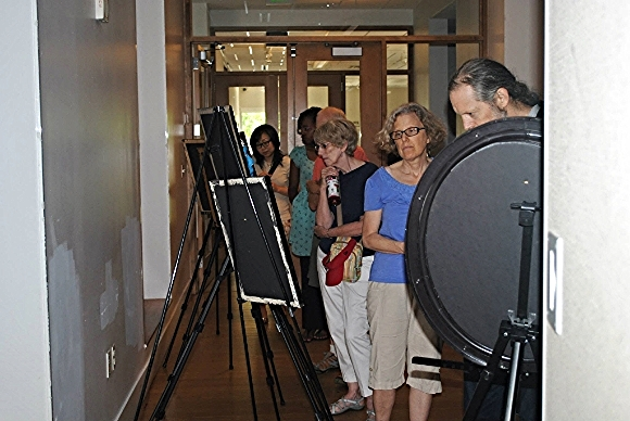 Attendees view an art exhibit at Gandhi Brigade Youth Media Festival