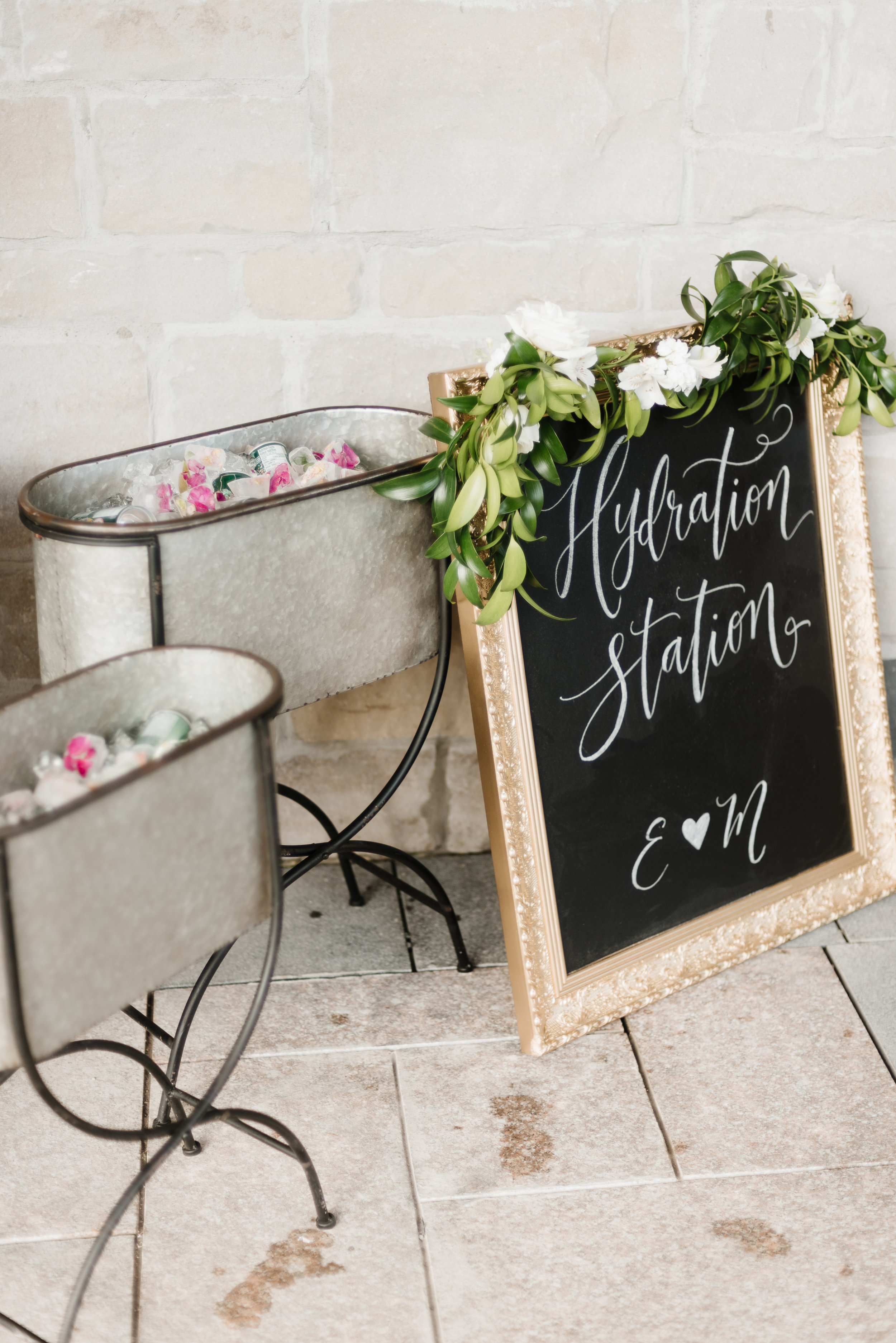 Water Station!  If you're planning a summer wedding, especially if it will be outdoors, you'll need something to keep your guests cool and refreshed. A drink station can do exactly that! We added custom signage and flower petal ice cubes for an added touch!  Photo:  Mango Studios   Calligraphy:  The Lettering Studio