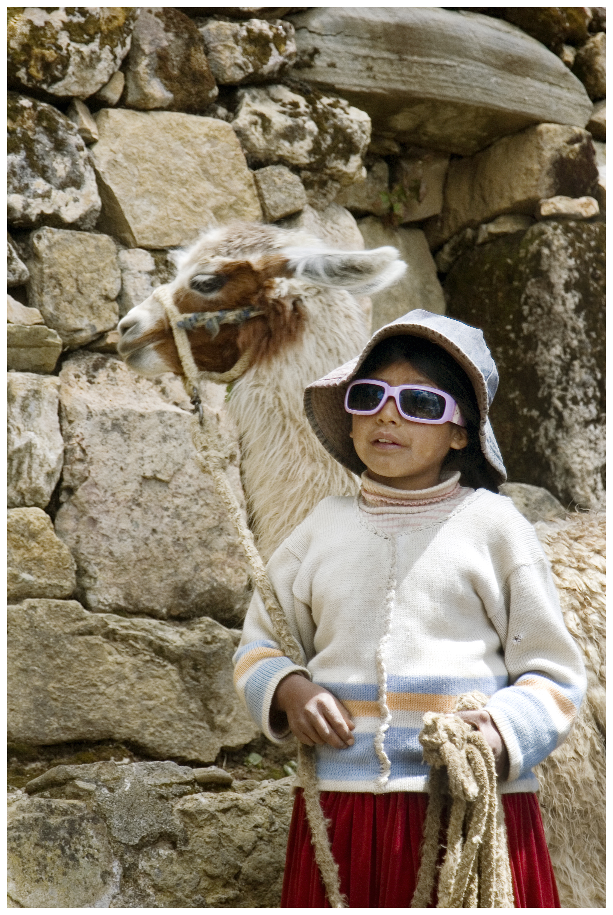 A young girl on The Island of the Sun (Isla del Sol) at Lake Titicaca walks her llama (pronounced yama) to drink water at a nearby spring.  The island is very isolated and only visited by boat.  The boat ride from Copacabana, Bolivia is about one hour.  Sunglasses make a nice gift, or a powerful trading commodity, to the locals.