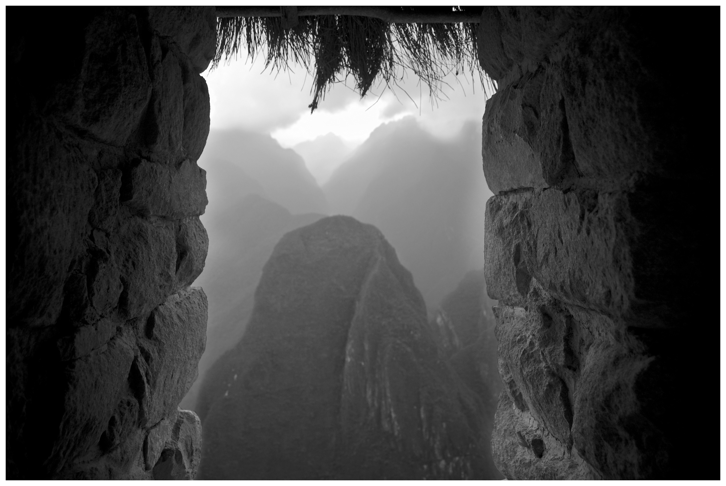 Distant peaks ascend as I peer through an existing window at Machu Picchu.