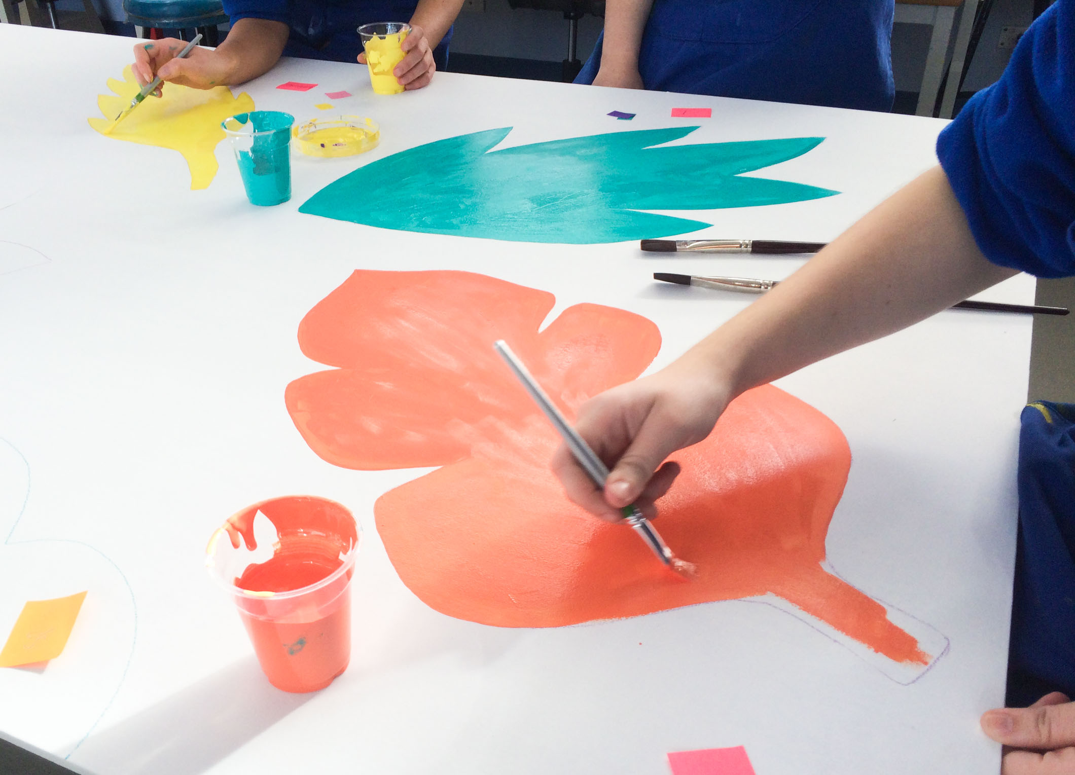 Students assisting in the painting of mural