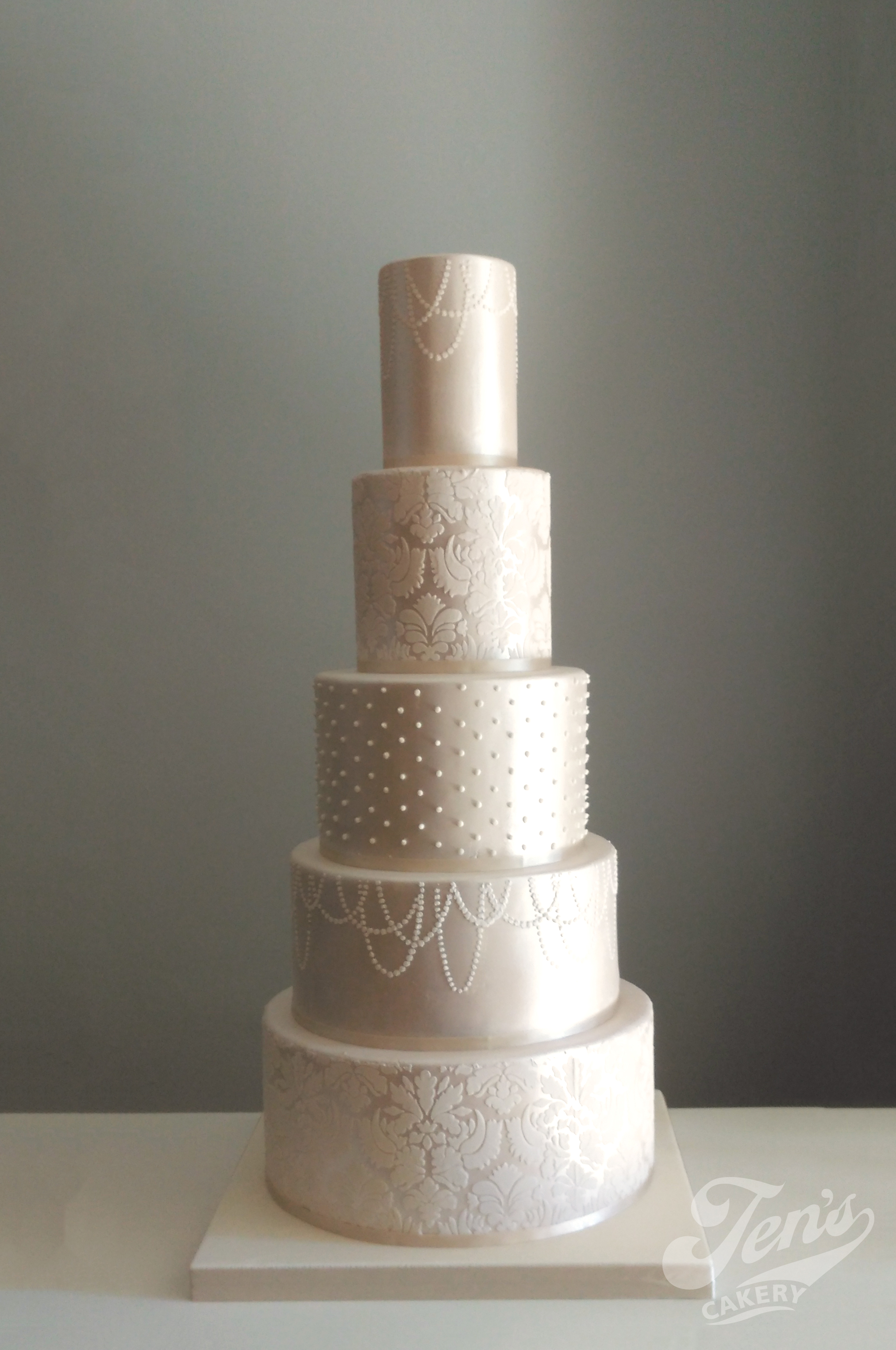 Satin wedding cake with extra deep tiers, lace and pearl finish. A tall cake with 5 tiers at the Langham in Central London.