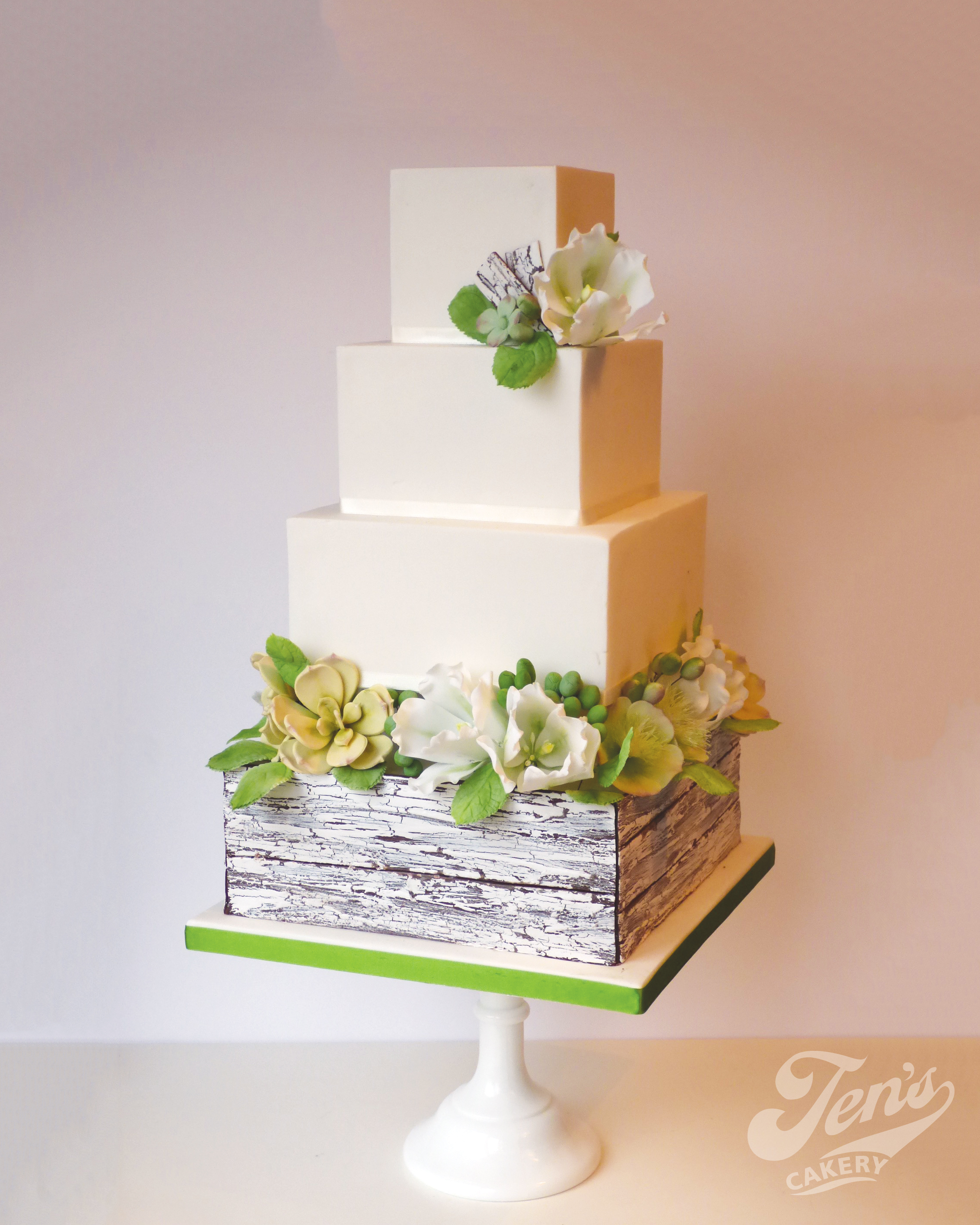 A square wedding cake with distressed painted crate, greenery foliage and sugar flowers.